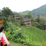 Beautiful wooden homes in the rice terraces, Yao woman in traditional clothing.
